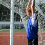 Senior Tommy Kerr takes a minute to stretch using the goal bars. Photo by Annie Lomshek