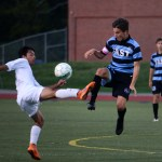 Senior Olivier Bihuniak jumps with a South player to gain possession of the ball. Photo by Kaitlyn Stratman