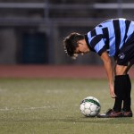 Senior Oliver Bihuniak bends down to fix his shin guards before taking a goal kick. Photo by Kaitlyn Stratman