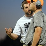 On the sidelines, coach Delaney talks to Coach Ufford about the play. Photo by Kaitlyn Stratman