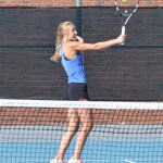 Senior Gretchen Cooper swings her racket to hit the tennis ball during the match. Photo by Katherine Odell
