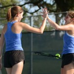 "Varsity doubles partners Caro Bush and Joie Freirich high five each other between points. Freirich said ""High-fiving is good because doubles is all about communication and it helps remind myself and my partner that it's a team effort"". Photo by Annie Lomshek"