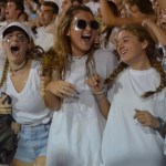 Juniors Amara Ivancic, Grace Stolberg, and Sophie Smith cheer as the the team scores a touchdown. Photo by Izzy Zanone