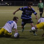 Senior Wil Krebs runs between the defenders to advance towards the goal. Photo by Izzy Zanone