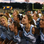 Senior Hope Hess laughs while varsity cheer chants in the beginning of the game. Photo by Morgan Browning