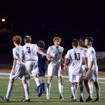 Senior Tommy Kerr high fives some of his teammates after East just scored a goal. Photo by Katherine Odell