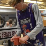 Freshman, Peter Kohring uses the sanding tool to smooth down his cutting board. Photo by Grace Goldman