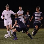 Senior Clayton Phillips dribbles past a Mill Valley defender as he runs the ball down the field. Photo by Haley Bell