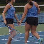 Tennis doubles partners junior Grace Chisholm and Sophomore Megan Walstrom give each other a high five after every point. Photo by Izzy Zanone
