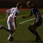 Junior Max Maday keeps the ball away from the opponent. Photo by Izzy Zanone