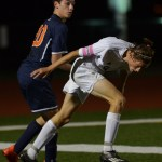 Senior Clayton Phillips heads for the ball, while blcoking his opponent. Photo by Izzy Zanone