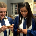 Sophomores Sophie Egan and Ella Stotts play on their phones before going on stage. Photo by Maddie Smiley