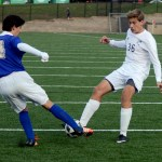 Sophomore Harrison Gloe fights for the ball with a Rockhurst player. Photo by Maddie Smiley