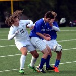 Sophomore Austin Brende tries to move around two opposing players to get the ball. Photo by Maddie Smiley