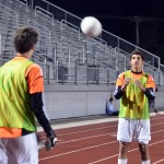 Sophomore Brandon McGaugh catches the ball from another goalie junior Nick Gasperi as they warm up to go into the game. Photo by Katherine Odell