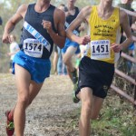 Senior John Arnspiger runs the course next to Blue Valley High School runner. Photo by Carson Holtgraves