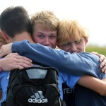 Junior Sam Ragland is hugged by Junior Ian Schutt and Senior Stanley Morantz at the end of the game. Photo by Kaitlyn Stratman