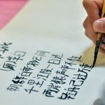 One of the Chinese Club members writes in Chinese symbols for the calligraphy contest. Photo by Libby Wilson