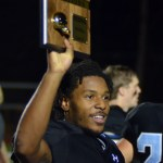 Senior Nigil Houston holds up the Regionals Champs plaque while walking off the field. Photo by Izzy Zanone