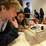 """Seniors Bryce Ainslie and Lydia Wickey look at another group's project after finishing their own. """"It was fun because they wanted us to learn and they made a point to discuss oppression,"""" said Wickey. Photo by Sophie Storbeck"""
