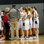 The Lady Lancers varsity basketball team huddles up during a time out. Photo by Luke Hoffman