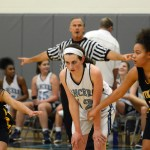 Sophomore Elizabeth Ballew is guarded by two players from Shawnee Mission West as they wait for someone to shoot a basket. Photo by Katherine Odell