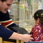 Senior Lars Troutwine tries perching a bird on the arm of a little girl before the bird flaps his wings. Photo by Lucy Morantz