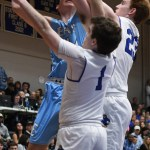 Senior Connor Reig tries to shoot the ball while two defenders are guarding him. Photo by Carson Holtgraves