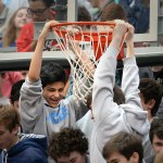 Surrounded by the freshman section, Ben Walburn hangs from the basket at the end of the assembly. Photo by Kaitlyn Stratman