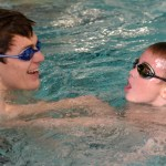 Junior Elias Lowland teaches one of the younger swimmers how to do a freestyle flip turn. Photo by Libby Wilson