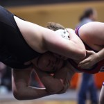 Sophomore Cooper Lovelace holds his opponent's head in the beginning of his last match. Photo by Morgan Browning