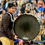 Junior Sid Chaudhary accompanies the yell leaders while a new chant is taught to the audience. Photo by Maddie Smiley