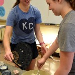 Juniors Madeline Hlobik and Isabelle Epstein work together to mix more rice and fan it so that it can be used to make the sushi rolls. Photo by Ellie Thoma