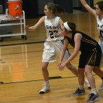 Freshmen Camryn Gossick and Kathleen Stanley, along with junior Caroline Blubaugh try to guard the post. Photo by Ty Browning