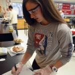 Junior Madeline Hlobik writes down data from her lab. She is testing which sports drink is best to rehydrate muscles. Hlobik is using dehydrated chicken muscles to act has our muscles in this experiment.  Photo by Izzy Zanone