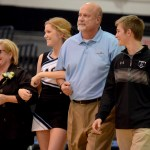 Senior Hope Hess walks across the gym floor with her family, Brenda Hess, Jim Hess, and sophomore Ryan Hess, during senior night. Photo by Maddie Smiley