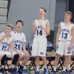 The Boy's Freshman team on the bench react to Freshman Luke Hanson's successful shot. Photo by CJ Manne