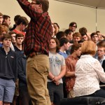 """Choir director, Ken Foley, signals for the soprano section to go higher in their song """"Voices of Earth"""". Photo by Lucy Morantz"""