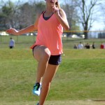Junior Madeline Stump pushes off the ground to further he jump. Photo by Katherine McGinness