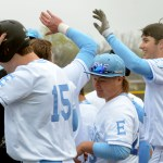 Senior Henry Miller gives high fives to his teammates after hitting a home run. Photo by Izzy Zanone