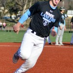 Junior Jonah Watt rounds the base while making a funny face at his teammates. Photo by Izzy Zanone