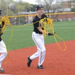 Freshmen Max Tucker and Scott Nicolarsen  run to plug in the cord for the pitching machine. Photo by Morgan Plunkett