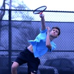 Sophomore Oliver Broce serves the ball to his opponent during a doubles match. Photo by Maddie Smiley