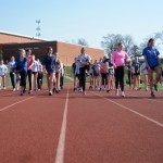 Track girls warm up before practice, doing leg stretches back and forth on the track. Photo by Ava Simonsen