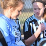 JV soccer coach Emily Flet runs through all of the plays before the scrimmage with the team. Photo by Reilly Moreland