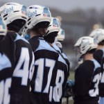 The Varsity Lacrosse team watches the game intensely from the side line. Photo by CJ Manne