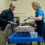 Junior Kirsten Erickson serves a taco to a donor from the church. Photo by Luke Hoffman