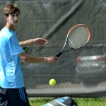 Junior Alex Paris returns the ball in his doubles match. Photo by Luke Hoffman
