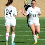 Sophomore Kate Hembree and sophomore Adelaine Marrone high five as Hembree subs in for Marrone in the second half of the game. Photo by Luke Hoffman