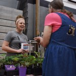 A woman discusses plants with a community gardener at the fair. Photo by Diana Percy